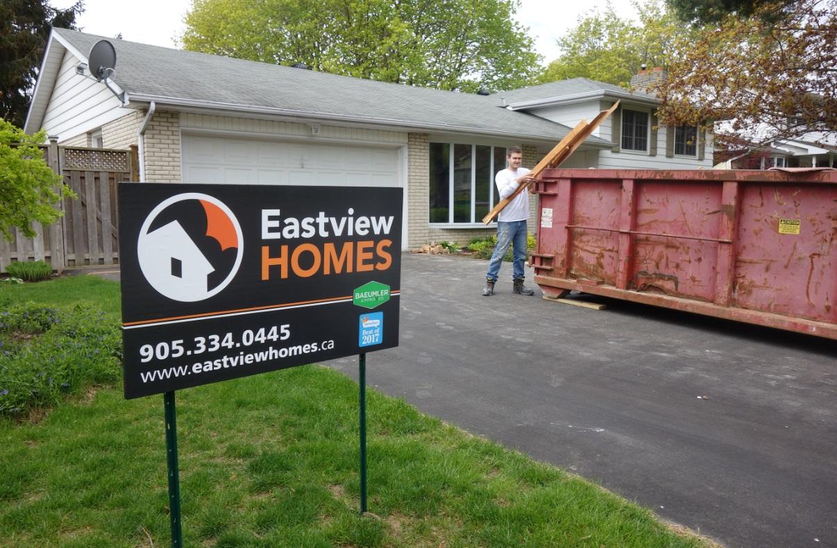Eastview Homes building project construction site - demolition job into metal materials bin