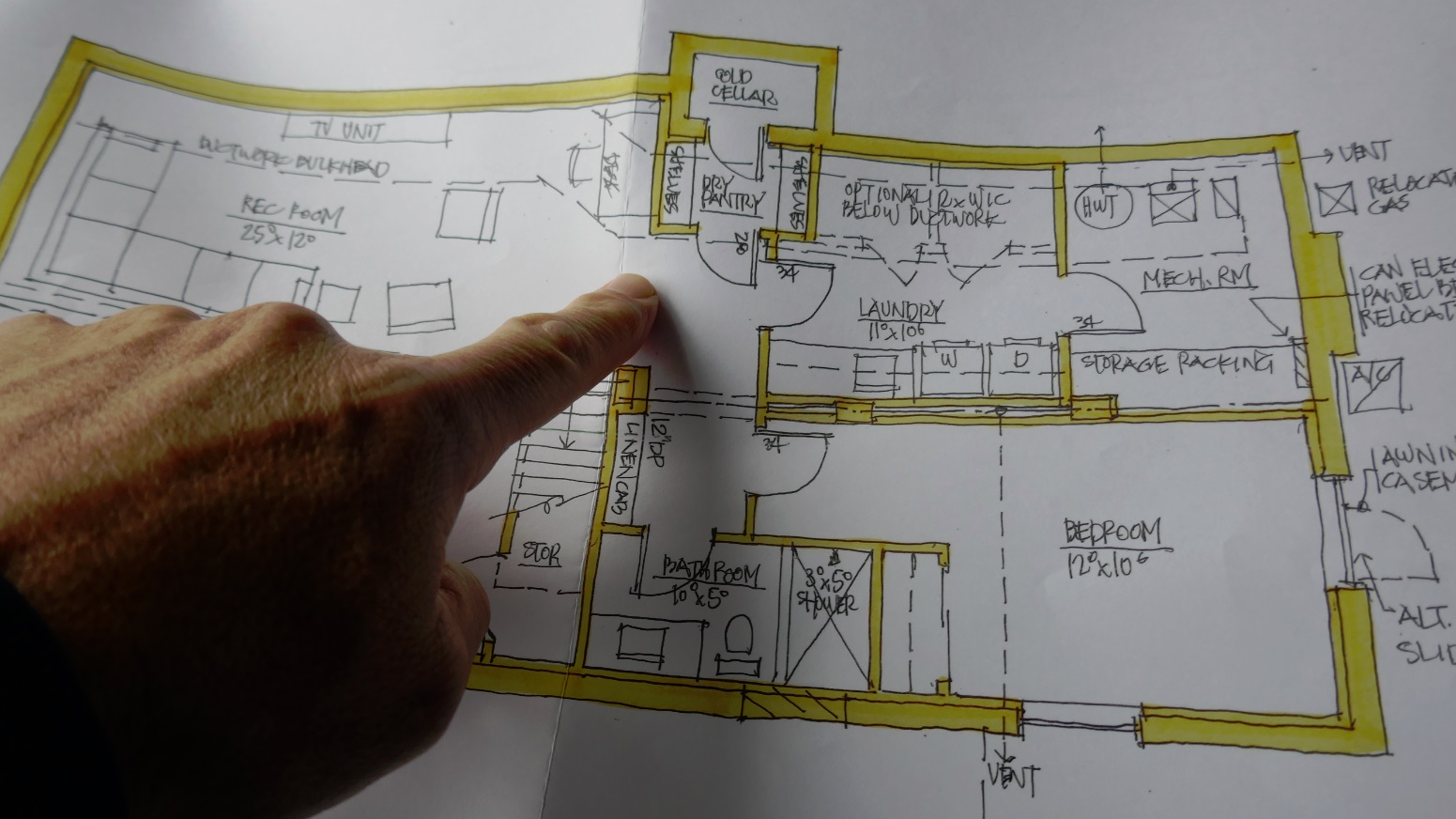 finger on blueprints showing a cold cellar, not a wine cellar