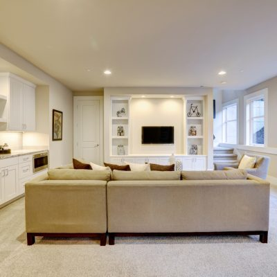 basement living room with wet bar, tv, windows
