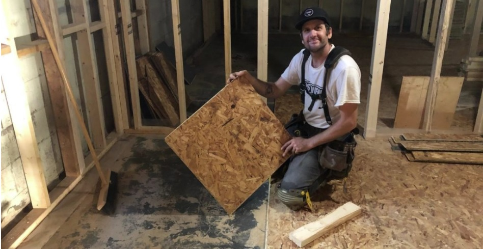 Eastview employee installs Dricore sub floor particle board panels in residential basement
