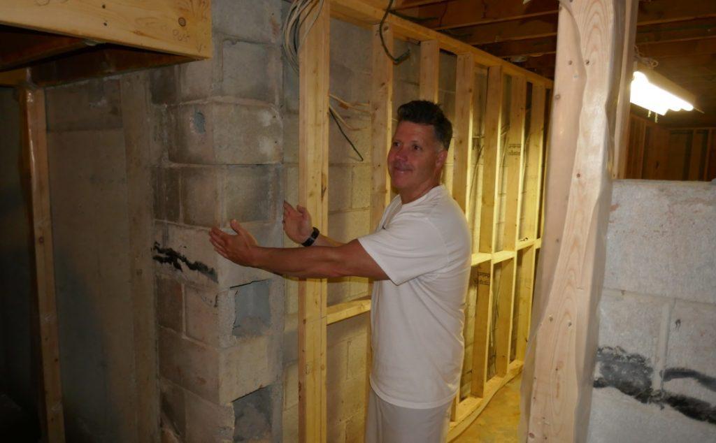 Construction manager shows basement cinder block wall width.