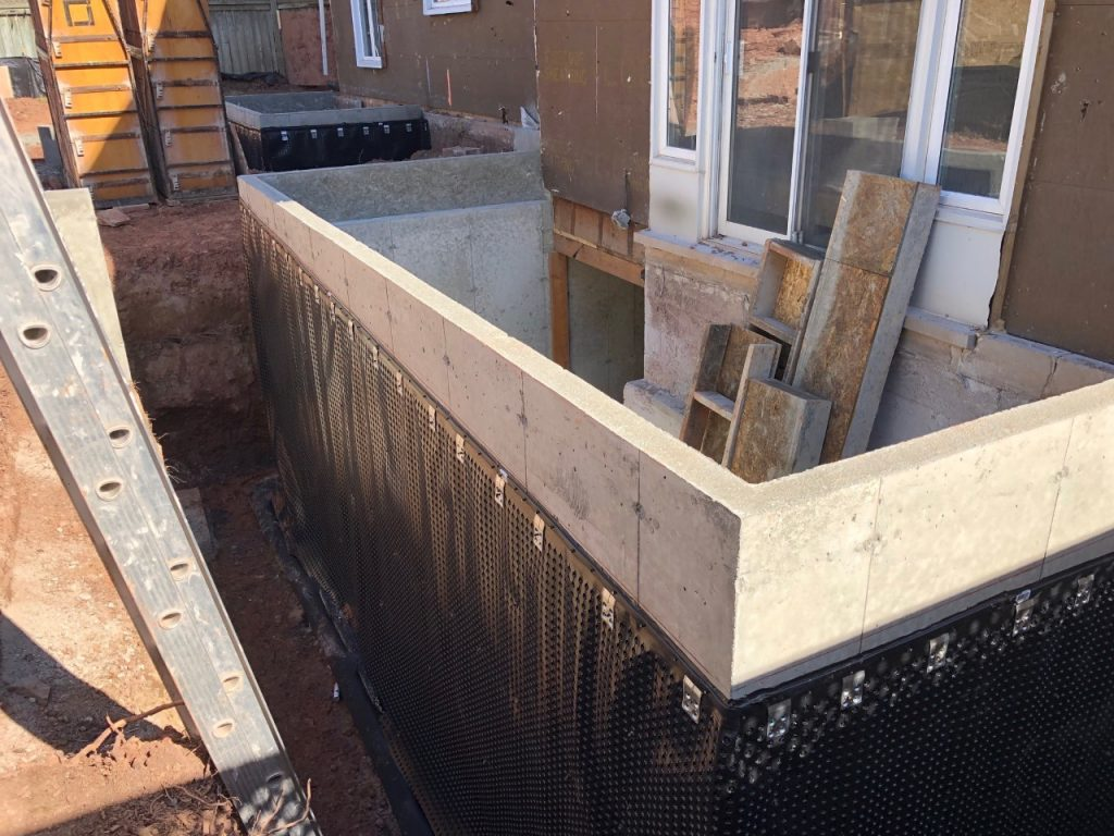 Concrete foundation wall with plastic resin membrane for waterproofing.